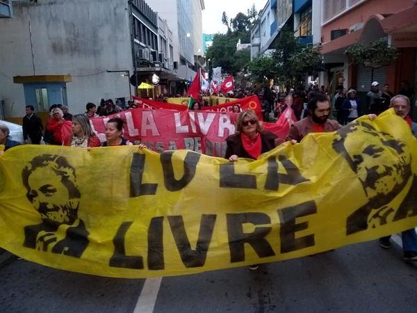 Manifestantes e a bandeira Lula Livre.
