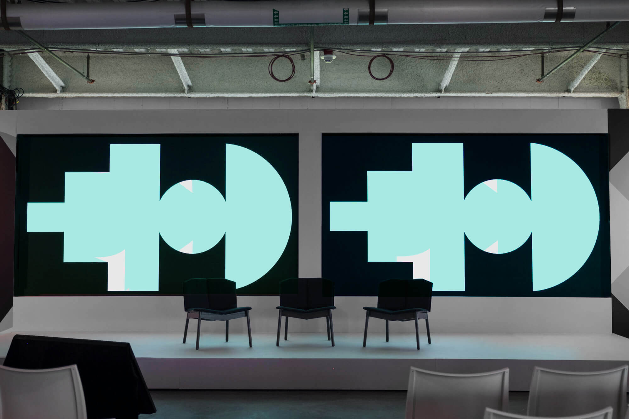 Photo of a stage with the Google SPAN conference screens on displays