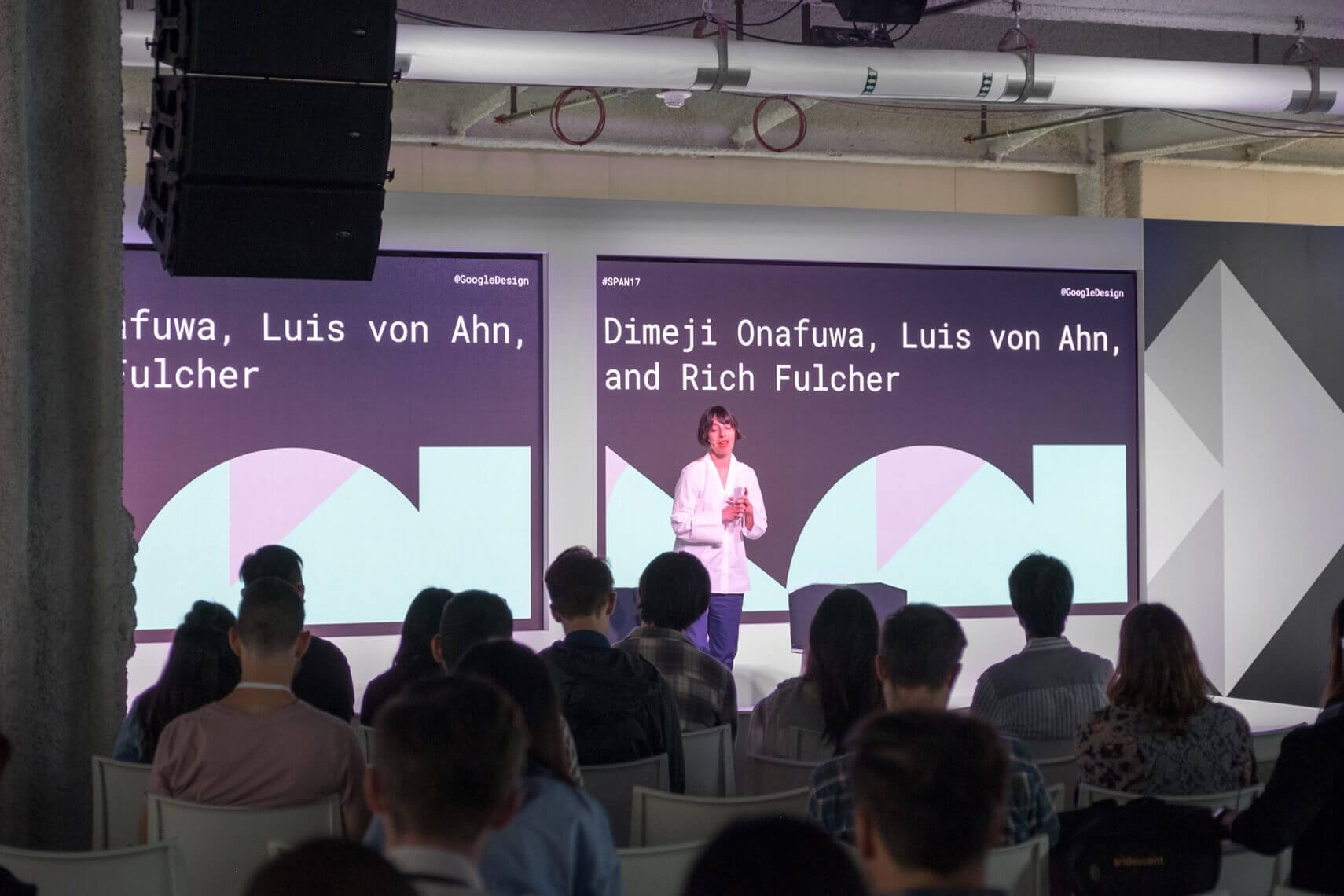 Photo of stage with woman giving speech and Google Span shapes on displays