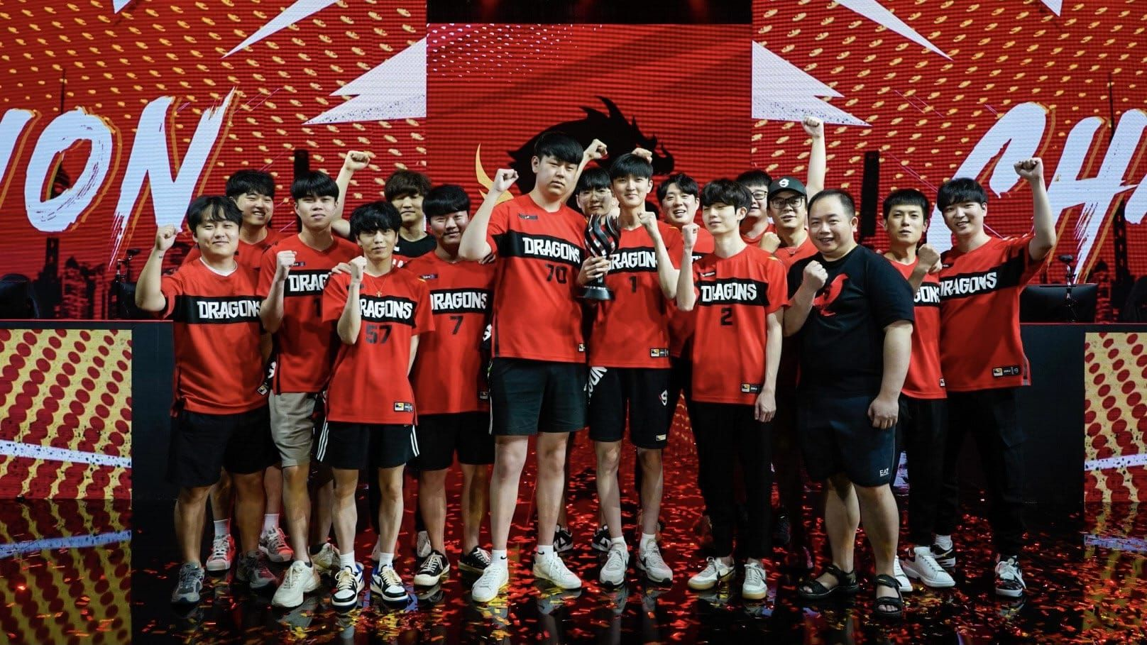 Shanghai Dragons Overwatch team on stage raise their hands up in the air after winning 2021 championship