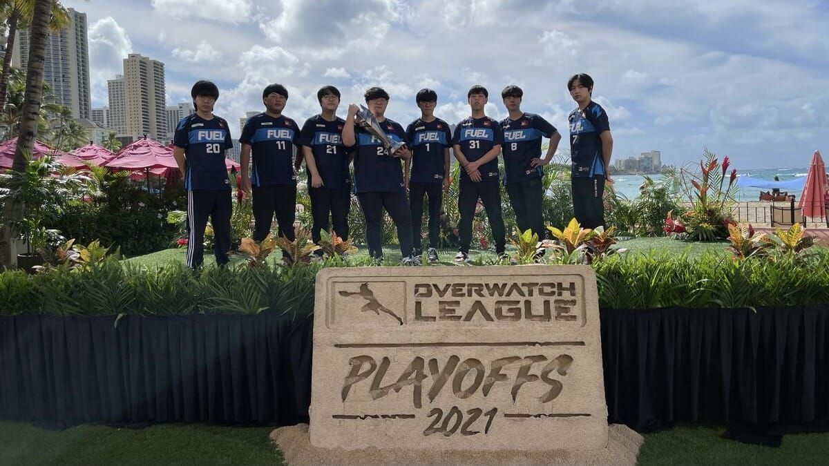 Dallas Fuel Overwatch team pose by the beach in Hawaii with Overwatch League 2021 playoffs sign