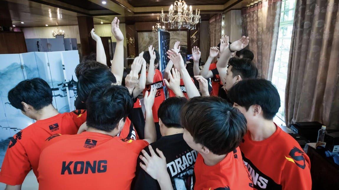 Shanghai Dragons Overwatch team in a team huddle raising their arms in the air