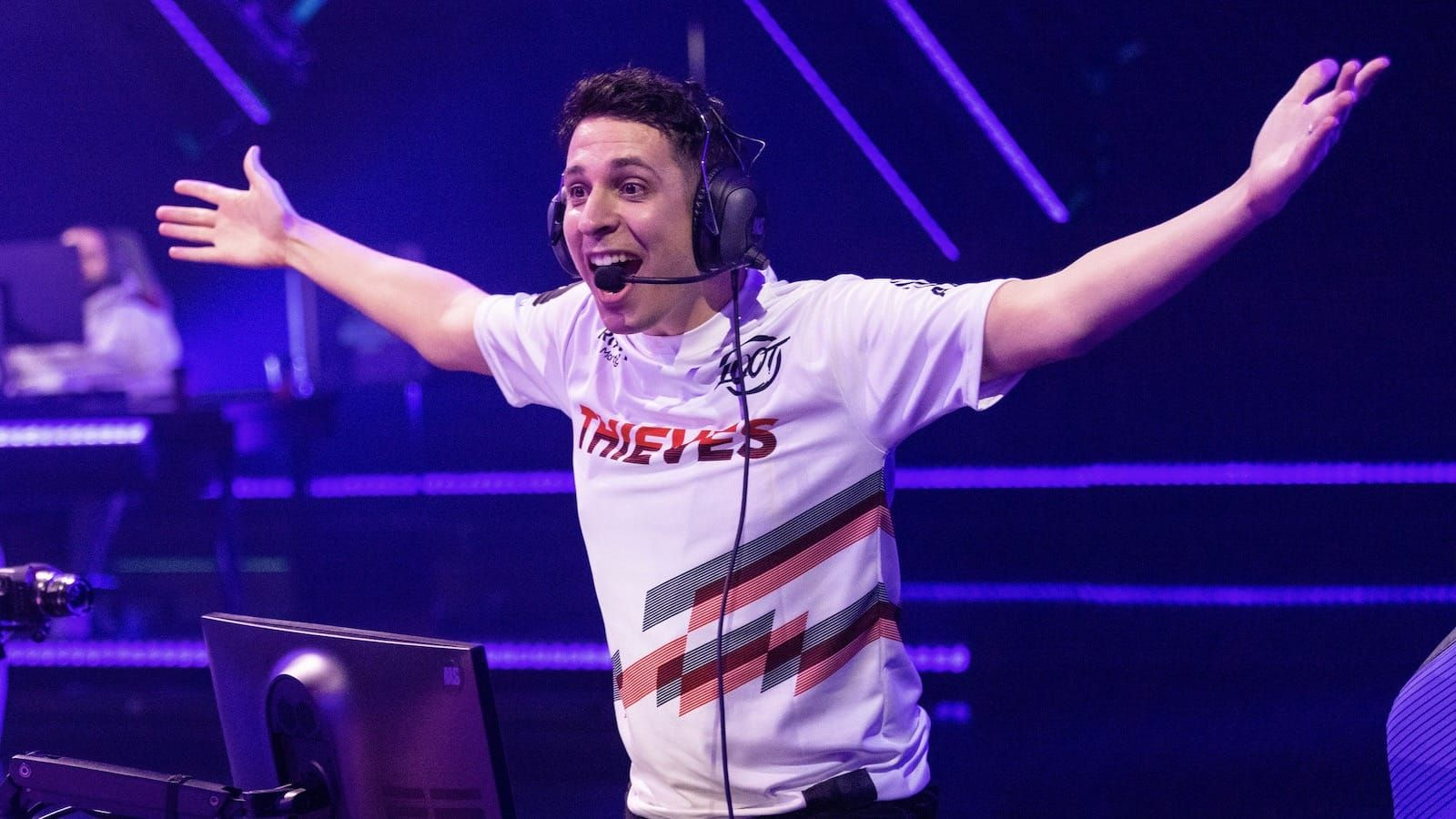 100 Thieves Valorant player steel standing up on excitedly on stage with arms spread wide