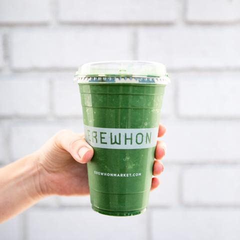 Hand holding green juice